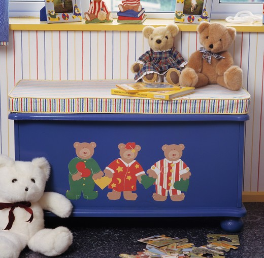 Teddybears sitting on striped cushion on blue chest with painted teddybears : Stock Photo