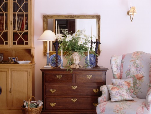 Stock Photo: 4291-18758 Floral wingchair beside antique chest-of-drawers in cottage living room