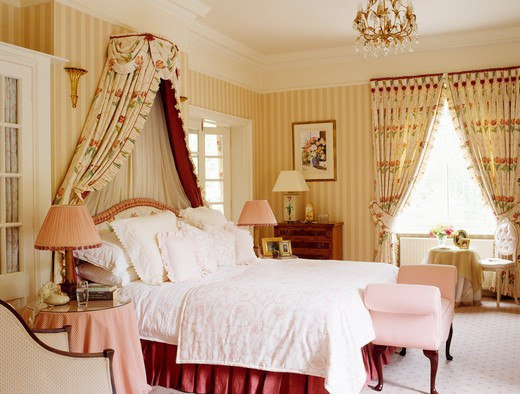 Coronet with floral drapes above bed in country bedroom with striped wallpaper : Stock Photo