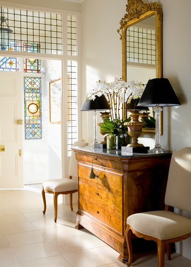Gilt mirror above antique chest-of-drawers with black lamps in traditional white hall with limestone floor tiles : Stock Photo