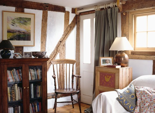 Stock Photo: 4291-19335 Antique bookcase and wooden chair in cottage livingroom with exposed wall beams