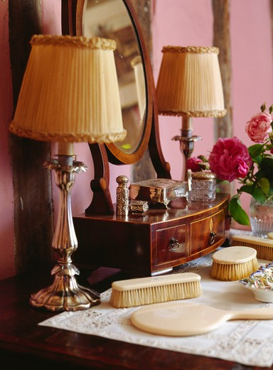 Close-up of metal lamps with cream ruched shades on dressing table with ivory brushes and hand-mirror : Stock Photo