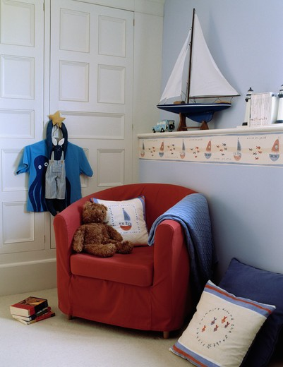 Teddybear with cushion and blue throw on red tub armchair in nautical-themed child's bedroom with sailing boat on shelf : Stock Photo