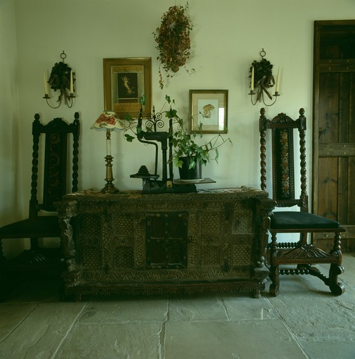 Stock Photo: 4291-20763 Antique Jacobean-style chairs on either side of carved wooden cupboard in country hall with flagstoned floor