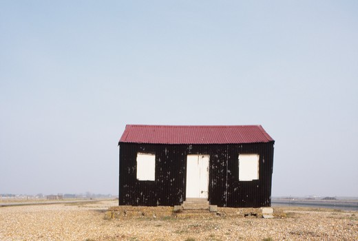 Stock Photo: 4291-20969 Black wooden hut with white shutters & door and corrugated tin roof at Rye in Sussex