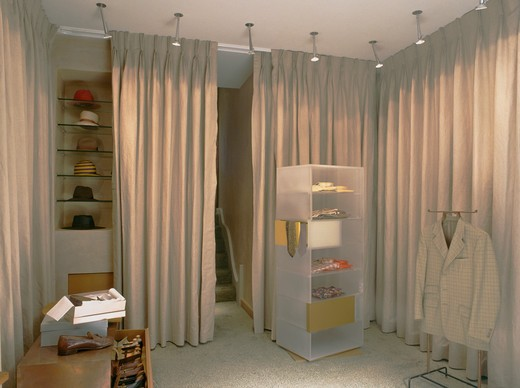 Spotlights above perspex shelving and beige curtains concealing storage : Stock Photo