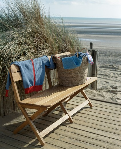 Basket of cloths on decking beside large beach : Stock Photo