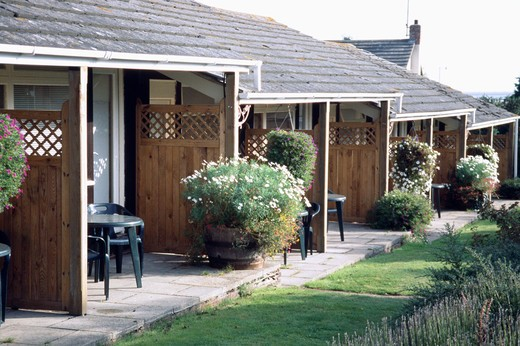 Stock Photo: 4291-21302 Patios and flowering plants in pots in front of ground floor rooms in country hotel in summer