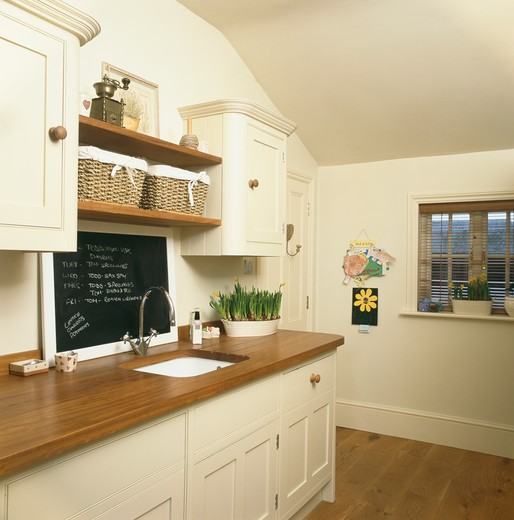 Stock Photo: 4291-22125 Blackboard above sink in wooden worktop in cream kitchen