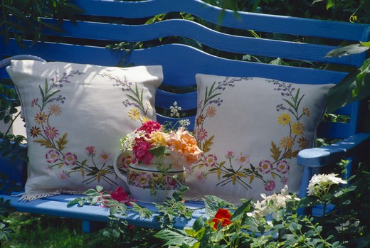 Still-life of roses and embroidered cushions on blue garden bench : Stock Photo