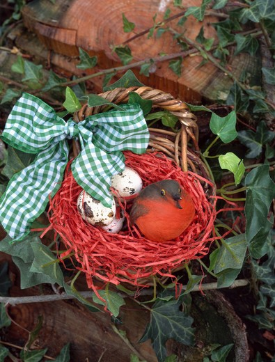 Stock Photo: 4291-22908 Close-up of felt robin with eggs in basket tied with green checked ribbon