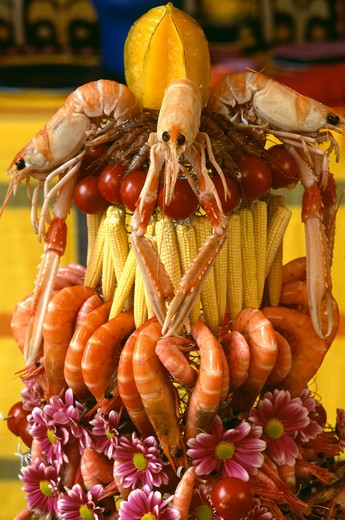 Close-up of table decoration of shellfish with small corn-on-the-cob and pink daisies : Stock Photo