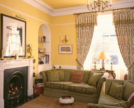 Patterned curtains and green sofas beside fireplace in yellow livingroom : Stock Photo