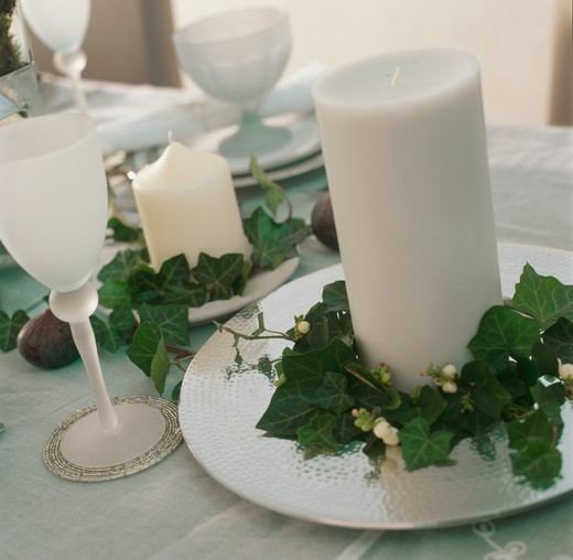 Stock Photo: 4291-23500 White frosted glass and white candle on white plate decoration with ivy leaf garland on dining table