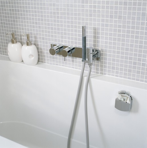 Modern white bath with chrome showerhead and taps : Stock Photo