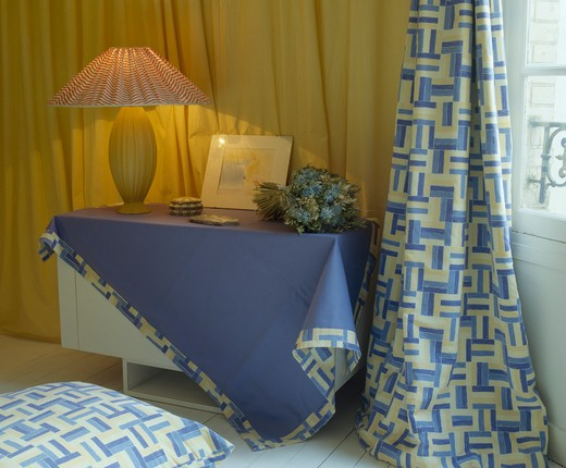Lighted lamp on table with blue cloth edged with patterned fabric and matching curtains in town bedoom : Stock Photo