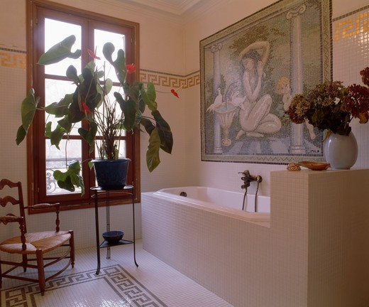 Stock Photo: 4291-24278 Large houseplant on table in front of window in bathroom with black and white tiled floor and mosaic picture above bath