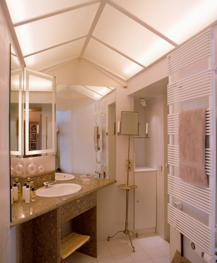 Lighted opaque glass panels on apex ceiling modern white bathroom with basin set into marble vanity unit : Stock Photo