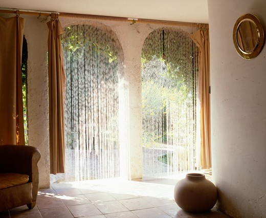beaded curtains on arched doorways in country