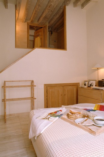 Stock Photo: 4291-24468 Breakfast tray on bed in modern bedroom with staircase to loft conversion bathroom