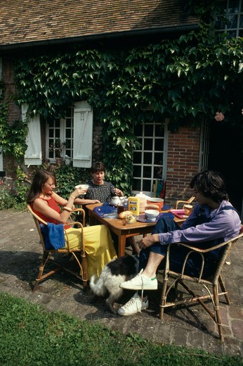 Stock Photo: 4291-24574 Children having tea at table outside French country house
