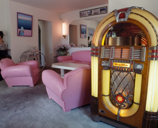 Wurlitzer jukebox in living room with pink leather armchairs : Stock Photo
