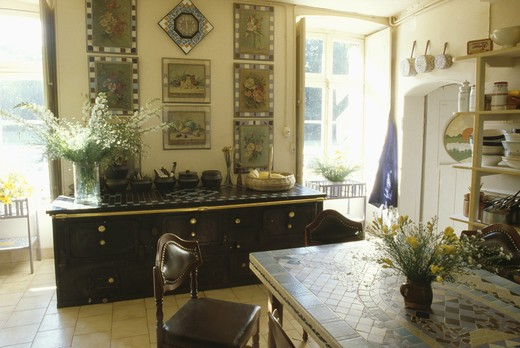 Stock Photo: 4291-25324 Mosaic-topped table and large black sideboard below group of pictures in French dining room
