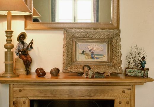 Close-up of old gilt-framed picture and blackamoor ornaments on pine mantelpiece : Stock Photo
