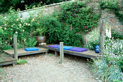 Stock Photo: 4291-4491 Blue cushions on wooden benches in country garden in summer