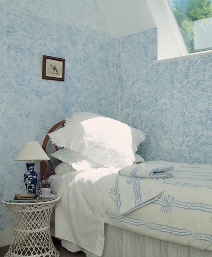 White pillows and blue and white duvet on bed below window in bedroom with painted stippled blue and white walls : Stock Photo