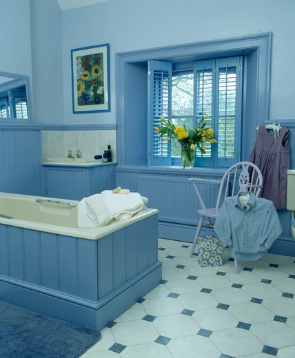 Blue plantation shutters in blue bathroom with tonque and groove panelled bath : Stock Photo