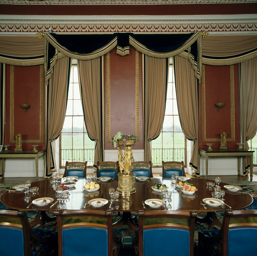 Stock Photo: 4291-6316 Ornate swagged curtains in large country house dining room with blue chairs and place settings on the table