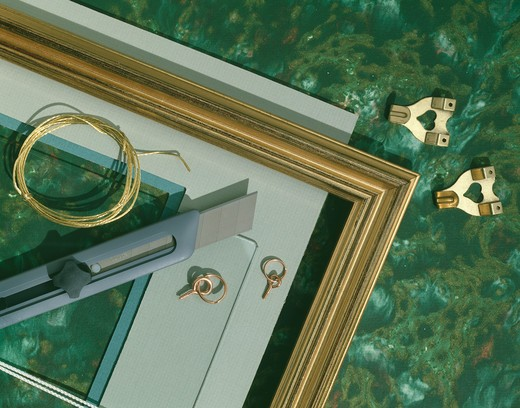 Close-up of gilt picture frame with Stanley knife brass wire and hooks : Stock Photo