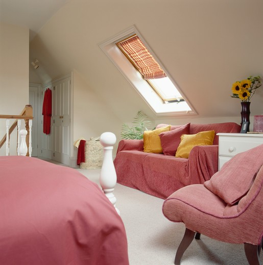 Stock Photo: 4291-8245 Pink throw and bedlinen in loft conversion bedroom with blind on velux window