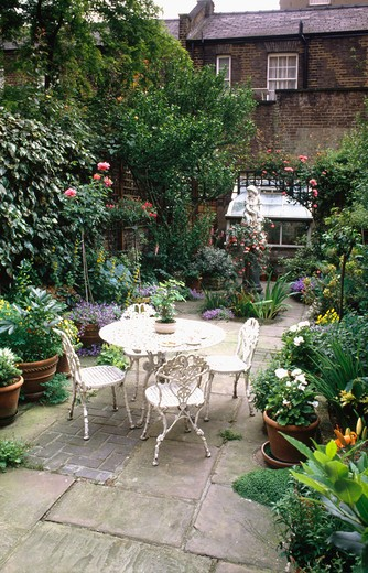 Stock Photo: 4291-8628 Plants in pots & white metal table and chairs on stone paved patio in town garden with statue and greenhouse