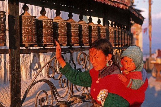 Stock Photo: 4292-106135 Nepal, Katmandu, woman at the Swayambhunath Stupa prayer wheels
