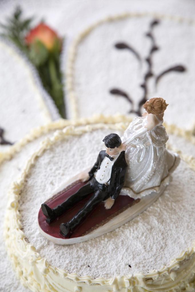 Humorous wedding figurines on cake : Stock Photo