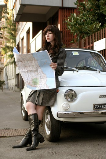 Man leaning on Fiat  Cinquecento car reading map : Stock Photo
