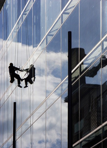 Ireland, Dublin, window washer in modern skyscrape : Stock Photo