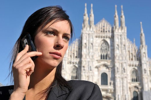 Italy, Lombardy, Milan. Businesswoman using mobile and view of the Duomo in background : Stock Photo