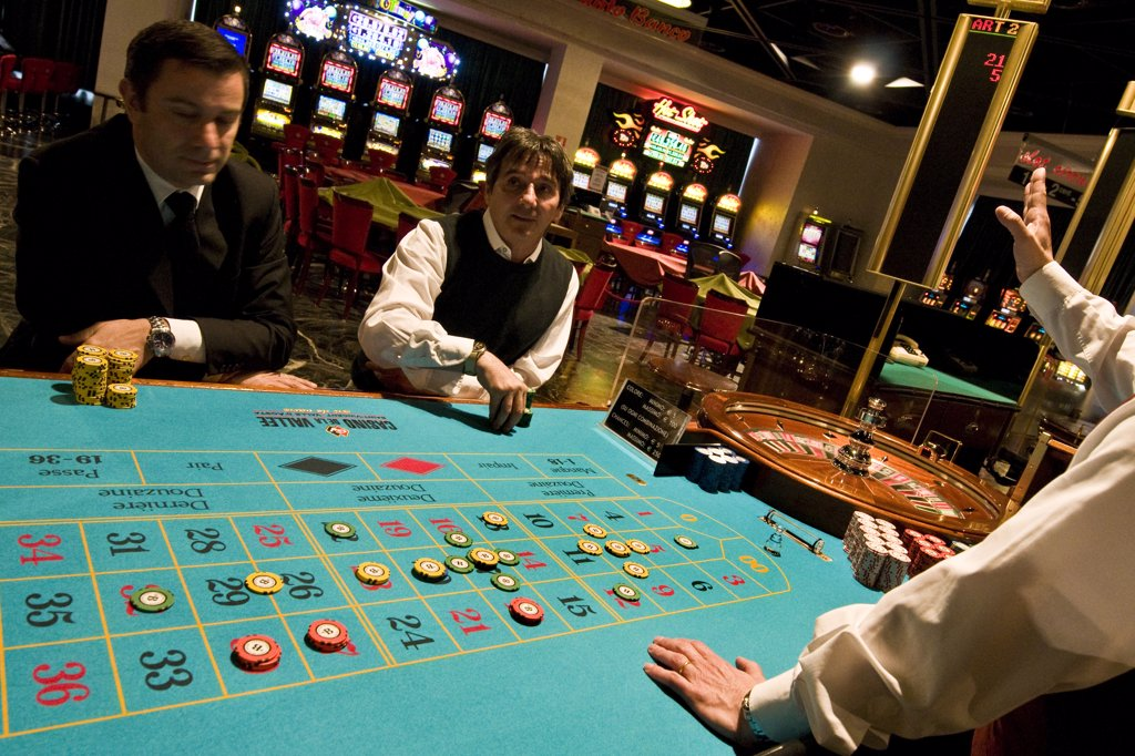 Italy, Val D'Aosta, Saint Vincent, people gambling at roulette table in casino : Stock Photo