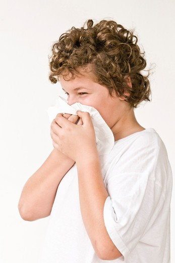 Boy blowing nose : Stock Photo