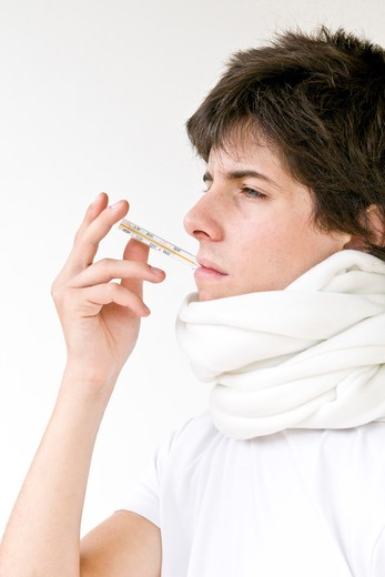 Teenage boy with thermometer in mouth : Stock Photo