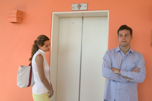 Stock Photo: 4292-12825 Couple in disagreement standing by door lift