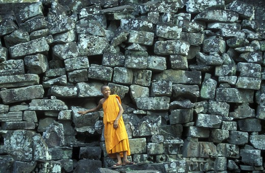 Stock Photo: 4292-130024 A monk before ruins to stones of the Bayon ruins in the Bayon temple in the ruins city of Angkor in Cambodia in southeast Asia.