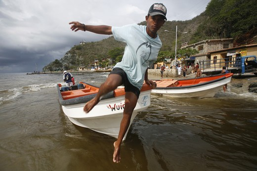 A boy jumps out of a taxi boat in Chuao in the Caribbean in Venezuela in South America. : Stock Photo