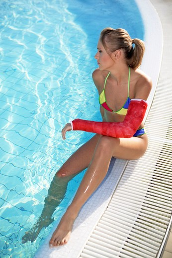 Stock Photo: 4292-130990 Frau mit geschientem Arm am Pool, woman with arm in a cast by the pool