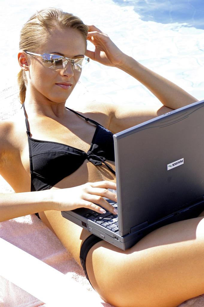 Junge Frau arbeitet mit einem Laptop am Pool : Stock Photo