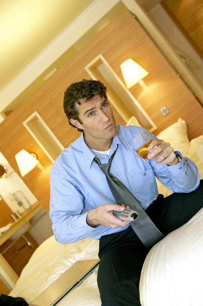 Stock Photo: 4292-131152 Manager beim Fernsehen seinem Hotelzimmer, man look at tv in hotel