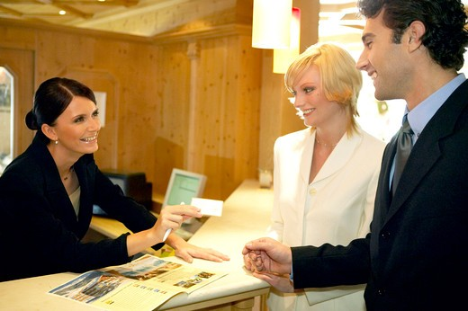 Stock Photo: 4292-131175 Paar beim Einchecken an der Hotelrezeption, couple checking in at reception desk of hotel